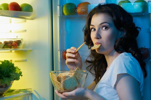 An hungry girl opens the fridge