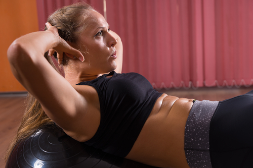 Young Woman Doing Ab Crunches Using Exercise Ball